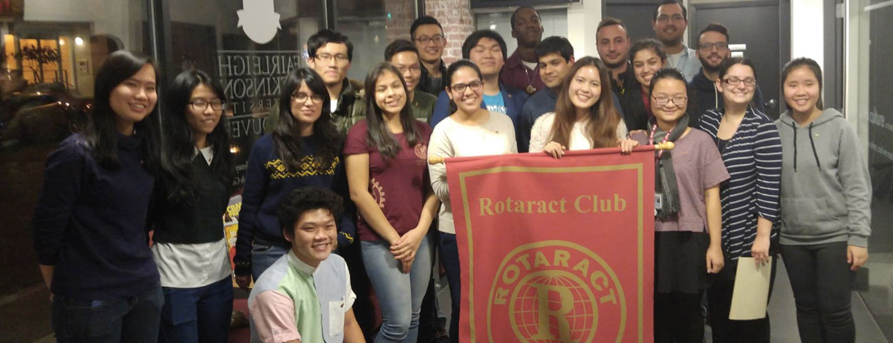 Vancouver Yaletown club members posing with a Rotaract banner